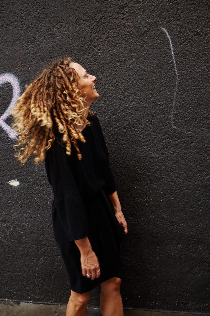 Julia steht lachend vor einer schwarzen Wand